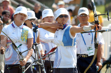 Korean archer Yun Mi Jin, foreground, takes aim at the target as teammates, from left, Park Sung Hyun, Lee Huyn Jung, Park Mi Kyung, and coach Ungaki Baek, look on during the Women's Recurve finals at the 42nd World Archery Championship, in New York. The Korean team defeated the Japanese team 252 points to 233 points