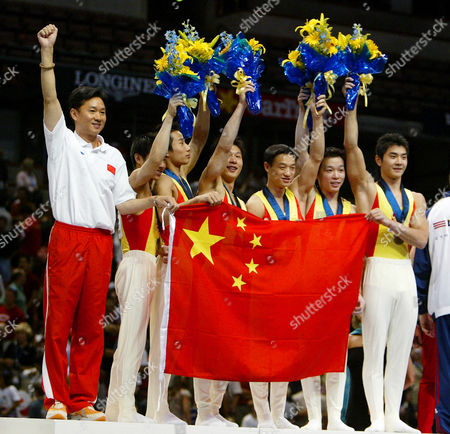 XING China's gold medal winning team members, from left, coach Yu Bin Huang, Haibin Teng, Qin Xiao, Xiao Peng Li, Wei Yang, Xu Huang, Aowei Xing, hold the Chinese flag as they celebrate after winning the men's team finals at the 2003 World Gymnastics Championships, in Anaheim, Calif