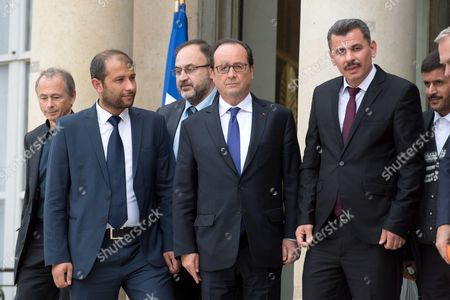 French President Francois Hollande (C), French deputy Elisabeth Guigou and French Foreign Minister Jean-Marc Ayrault pose with Raed Saleh, head of the White Helmets, and a Syrian delegation from Aleppo