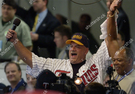 """VENTURA OLIVA Minnesota Gov. Jesse Ventura, right, and Minnesota Twins Baseball Hall of Famer Tony Oliva, wave to the crowd after signing """"Take Me Out To The Ball Game"""" during the seventh inning stretch at Game 2 of the American League Championship Series, between the Twins and the Anaheim Angels, in Minneapolis"""