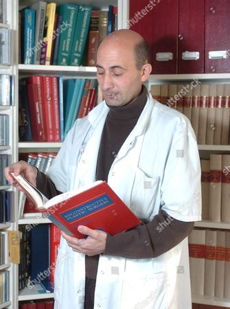 Dr. Laurent Lantieri reading a copy of 'Reconstructive Plastic Surgery'. He has performed another face transplant on a 29 year old man, who they have given a new nose, mouth and chin and sections of his cheeks