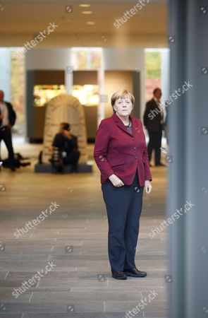 German Chancellor Angela Merkel waits for the French president Francois Hollande prior to a meeting in the Normandy format with Russian President Vladimir Putin and Ukrainian President Petro Poroschenko at the chancellery