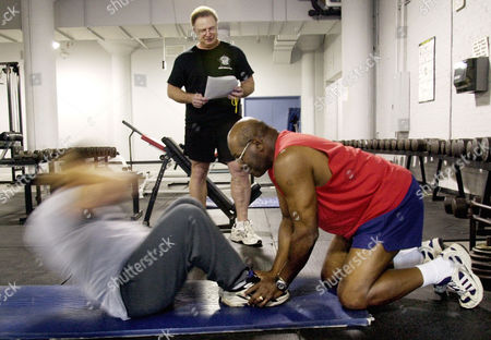 LAYMAN COLLINS AMOS Chicago Police Department instructor Ray Collins observes as Officer Richard Layman, left, with the help of fellow Officer Al Amos, does sit-ups during the department's voluntary physical fitness test, in Chicago. The police department offered an incentive of $250 for any officer who could pass the test. About 2,400 passed of the 2,600 that have participated so far
