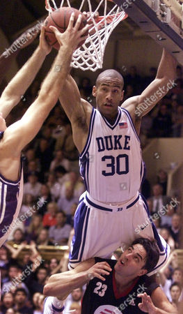 JONES CANTRELL Duke's Dahntay Jones (30) goes over the back of EA Sports All-Stars' Damien Cantrell (23) as he battles a teammate for a rebound during the first half of, game being played at Cameron Indoor Stadium, in Durham, N.C
