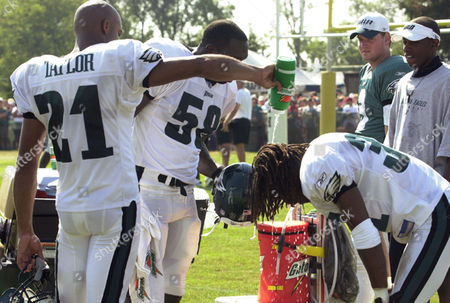 TAYLOR HARRIS Philadelphia Eagles Bobby Taylor, left, pours water over the head of teammate Al Harris during a water break at practice at the Eagles training camp in Bethlehem, Pa