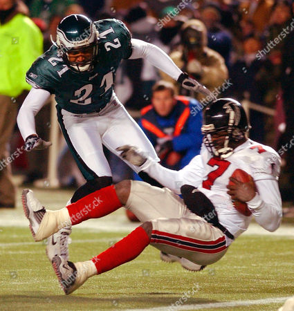 TAYLOR VICK Atlanta Falcons quarterback Michael Vick (7), falls to the ground after being hit by a Philadelphia Eagles defender in the second half of their divisional playoff game at Veterans Stadium in Philadelphia, Pa., . At rear is Eagles' Bobby Taylor
