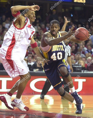 DARTEZ SANDERS Marquette's Terry Sanders drives past Louisville's Kendall Dartez during the first half of their game, in Louisville, Ky