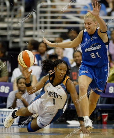 HOLDSCLAW SCHUMAN Washington Mystics' Chamique Holdsclaw, left, tries to pass the ball as she falls going up against Orlando Miracle's Stacey Dales-Schuman at the MCI Center in Washington. Orlando went on to win 70-55