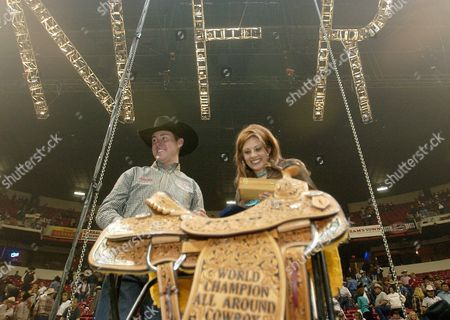 BRAZILE Trevor Brazile, of Anson, Texas, left, and his wife, Shada, stand next to the saddle he won for the title of all-around cowboy, after the 10th and final round of the National Finals Rodeo at the Thomas & Mack Center in Las Vegas