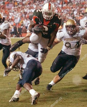 MCGAHEE SPENCER STEPHENS Miami running back Willis McGahee, center, leaps over Pittsburgh defensive back Shawntae Spencer for a touchdown during the second half at the Orange Bowl in Miami. At right is Pittsburgh defensive lineman Dan Stephens. No. 1 Miami beat No. 17 Pittsburgh 28-21