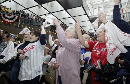 Minnesota Twins fans including Katherine Starzecki, left, Kara Scherbring, Ruth Johnson and Betty Smith, right, sing Take Me Out to the Ballgame, at a rally for the Twins at the IDS Center in Minneapolis, . The Twins play the Oakland Athletics in the American League division championship Friday at the Metrodome with the series tied 1-1
