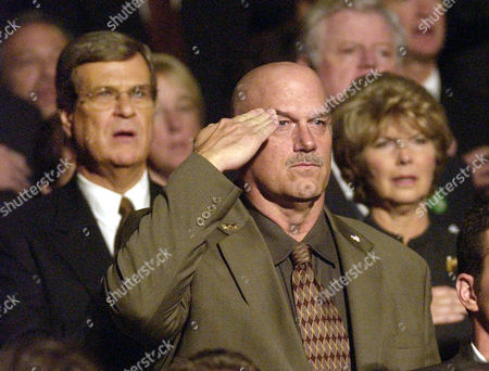 WELLSTONE MEMORIAL Minnesota Gov. Jesse Ventura salutes during the national anthem at the start of the public memorial service, in Minneapolis for U.S. Sen. Paul Wellstone, his wife, daughter and three staff members who died Friday in a plane crash in Eveleth, Minn. At left is Sen. Trent Lott