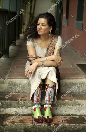 """CISNEROS Author Sandra Cisneros sits for a portrait in San Antonio, . """"You can't get famous in Texas,"""" she writes in her new novel, """"Caramelo,"""" but the 48-year-old Cisneros defies that theme as her fame grows from coast to coast"""