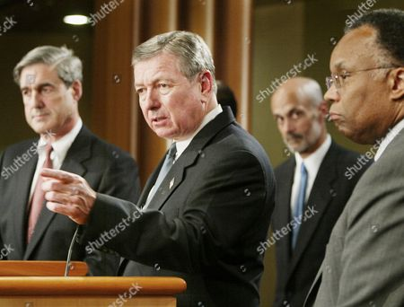 THOMPSON Attorney General John Ashcroft, second from left, accompanied by other officials. gestures during a news conference at the Justice Department in Washington to discuss WorldCom. Two former WorldCom executives were charged Thursday with hiding billions in expenses and lying to investors and regulators in a desperate bid to keep the company afloat. From left are, FBI Director Robert Mueller, Ashcroft, Michael Chertoff, head of the Department of Justice's criminal division and DeputyAttorney General Larry Thompson