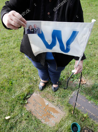 Terry Ann Arriaga holds a photo of her parents Norman and Florence Sanders along with a Cubs W flag that was placed over the couple's grave site at St. Luke's Cemetery, in Chicago. Mr. Sanders died in 2003 when the Cubs were within five outs of reaching the World Series and Mrs. Sanders died earlier this year during spring training