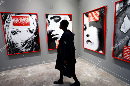 """Anna Alix Koffi, creative director of Off The Wall looks at """"Untitled (Project for Dazed and Confused) 1996/2015"""" by artist Barbara Kruger during the FIAC art fair at the Grand Palais, in Paris, . For this 43rd edition, France's FIAC art fair attracting over 186 galleries from around 27 countries, opens Oct. 20 and lasts until Oct. 23"""