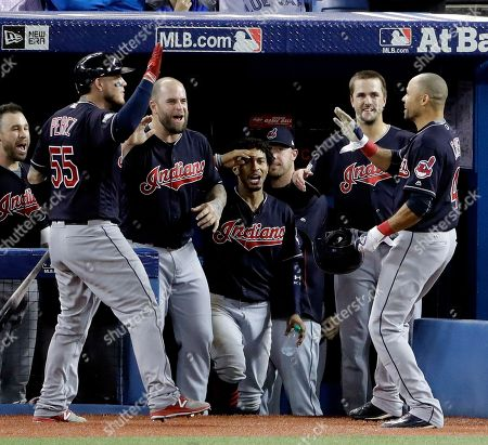 Cleveland Indians' Coco Crisp celebrates in the dugout after his home run against the Toronto Blue Jays during the fourth inning in Game 5 of baseball's American League Championship Series in Toronto