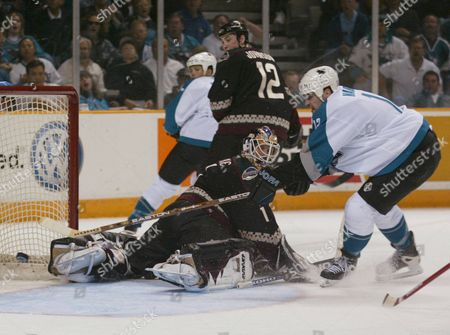 BURKE San Jose Sharks' Patrick Marleau, right, slips the puck past Phoenix Coyotes goalie Sean Burke as Coyotes' Mike Johnson, center, and Sharks' Todd Harvey look on during the second period of Game 5 of a first-round Western Conference playoff series, in San Jose, Calif