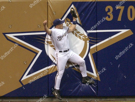 JENKINS LEWIS Milwaukee Brewers left fielder Geoff Jenkins hits the wall as he catches Chicago Cubs' Darren Lewis fly ball in the fifth inning in Milwaukee
