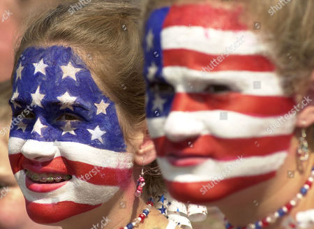 Kathy Brown, 12, left, and Caroline Atwater, 13, watch a Fourth of July parade in Catonsville, Md., . Hundreds of people lined Catonsville's streets to watch the parade despite hot temperatures and high humidity