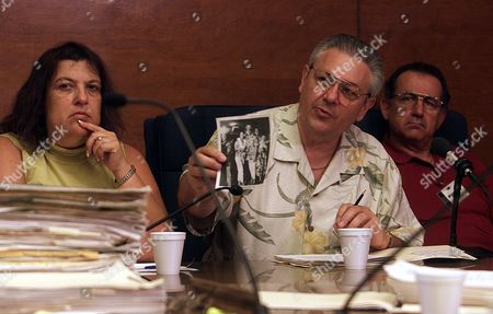 SMALDINO SMALDINO DESANTIS Angela Smaldino, left, Louis Smaldino, middle, and John DeSantis, family members representing the LaBianca family hold up an undated photo of their murdered relatives to show the members of the Board of Prison Terms commissioners during a parole hearing for Manson follower Leslie Van Houten, at the California Institution for Women in Corona, Calif. Van Houten, 53, who has served over 30 years in prison for her involvement in the Tate-La Bianca killings, was denied parole