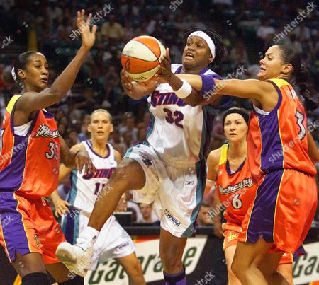 STINSON HARRISON WILLIAMS Charlotte Sting's Andrea Stinson (32) is fouled as she drives between Phoenix Mercury players Lisa Harrison, left, and Adrain Williams, right, in the first half at the Charlotte Coliseum in Charlotte, N.C
