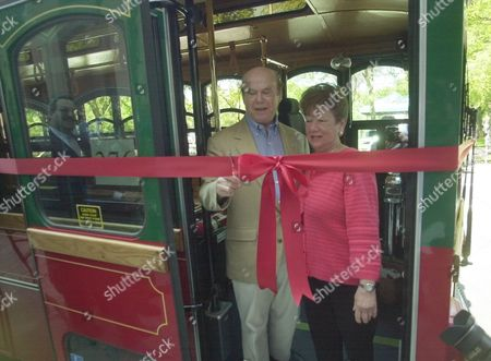 GLUCKSMAN Sidney Glucksman cuts the ribbon while his wife, Libby Glucksman looks on during a ceremony in New Haven, Conn., beginning electric trolley service in downtown New Haven. The Glucksmans, who saw the same type of trolley where they vacation, told New Haven Mayor John DeStefano about them and got him interested in the trolleys as a possibility for New Haven