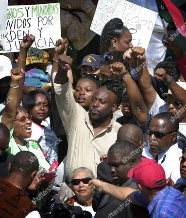 """Dozens of angry protesters wave signs and shout """"No justice, no peace,"""" outside the Inglewood, Calif., City Hall . The protest was against Inglewood police officer Jeremy Morse who was shown on a videotape he slammimg 16-year-old Donovan Jackson onto a squad car, then punching him"""