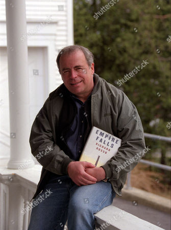 "RUSSO Richard Russo, winner of the Pulitzer Prize for fiction, holds a copy of the novel for which he won, ""Empire Falls,"" on the front porch of his home Camden, Maine"