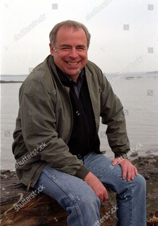 """RUSSO Richard Russo, winner of the Pulitzer Prize for Fiction for his novel, """"Empire Falls,"""" sits in front of Camden Harbor, Maine"""