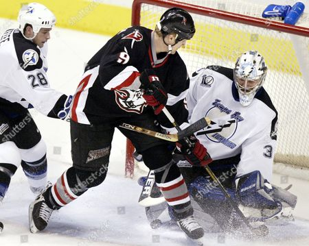 KEEFE KHABIBULIN RASMUSSEN Buffalo Sabres' Erik Rasmussen (9) takes a shot on Tampa Bay Lightning goalie Nikolai Khabibulin (35) of Russia while being tied up by the Lightning's Sheldon Keefe (28) in the first period, in Tampa, Fla. Khabibulin made the save