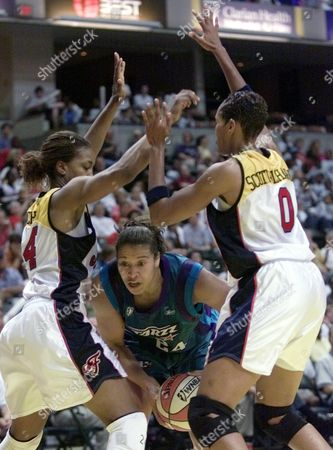 RICHARDSON Utah Starzz forward Natalie Williams, center, cuts between Indiana Fever forward Tamika Catchings, left, and Olympia Scott-Richardson as she drives to the basket in the second half in Indianapolis, . The Starzz won 82-69