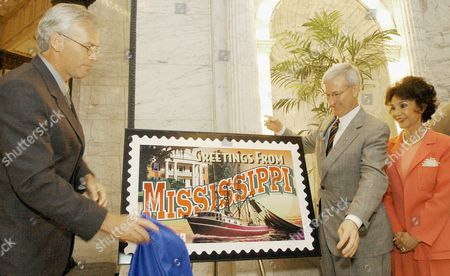 """MOBLEY KINCAID MUSGROVE Actress and former Miss America Mary Ann Mobley, of Brandon, Miss., right, watches as David Kincaid, marketing manager for the United States Postal Service, Mississippi District, left, and Gov. Ronnie Musgrove unveil Mississipp's stamp, one of the """"Greetings From America"""" series of stamps, at the Capitol in Jackson, Miss"""