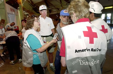 Stock Photo of ULIBARRI American Red Cross workers Carolyn Dinger, left, Richard Roelke, second left, Elaine Rogers, foreground with back to camera, Billy Barrera, far right, assist evacuee Robert Ulibarri, center with blue cap at Round Valley High School in Eagar, Ariz. Wildfires forced residents from several local communities to leave their homes