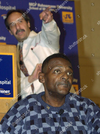 """QUINN Artificial heart recipient James Quinn, 51, of West Philadelphia, takes part in a news conference, with Dr. Louis Edward Samuels, rear, surgical director of the cardiac transplant team, at Philadelphia's Hahnemann University Hospital, where the three-hour surgery was performed on Nov. 5, 2001. Quinn, a retired baker and grandfather of five, and who was the world's fifth recipient of a self-contained artificial heart, said he was thankful for his faith and his doctors for givinghim a """"second chance."""" Hahnemann is one of five sites participating in trial studies involving the AbioCor heart"""