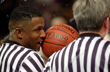 Refree Ted Valentine holds the ball in front of his face to block players from reading his lips while talking to refree John Cahill during a timeout between Villanova and Connecticut at the Big East basketball tournment Thursday, March, 7, 2002, in New York. Connecticut defeated Villanova 72-70