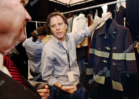 Designer Charles Nolan, right, shows a black and steel blue wool hip-length coat resembling a fireman's coat from his Anne Klein fall-winter 2002 collection, to his father, Phil Nolan, a former Hempstead, N.Y. firefighter, backstage before the show in New York. Nolan, known to have a passion for American classics but skew them with a modern edge and personal touch, died . He was 53