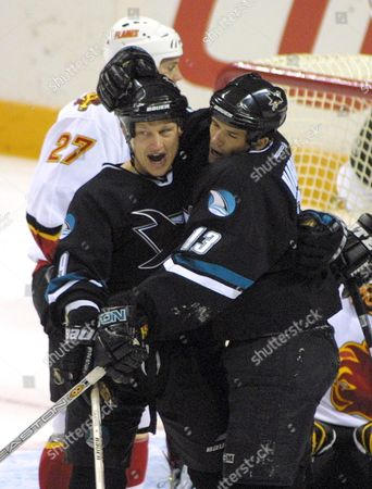 GRAVES HARVEY SAVARD San Jose Sharks' Adam Graves (9) is congratulated by Todd Harvey (13) after scoring against the Calgary Flames in the first period in San Jose, Calif., . The Flames' Marc Savard (27) is behind