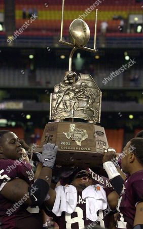 JONES BERNARD BROOKS Texas A&M's Mickey Jones (83) struggles to lift the trophy as he gets help from teammates Rocky Bernard, left, and Jay Brooks, right, after Texas A&M beat Texas Christian 28-9 in the Galleryfurniture.com Bowl, in Houston