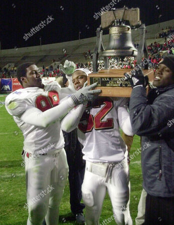 JACKERSON Louisville players Chad Lee (98) and Jonathon Jackerson (52) hoist the Liberty Bowl trophy after Louisville defeated Brigham Young, 28-10, in the Liberty Bowl on in Memphis, Tenn. The fan at right is unidentified