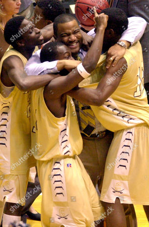 Stock Photo of ROBINSON Cummings players, from left, Edward Daye, Mike Enslow and Mike Hinton celebrate with coach George Robinson, center, during the closing seconds of the Class 2-A men's state championship game at the Dean Smith Center in Chapel Hill, N.C. Cummings defeated North Pitt 80-78