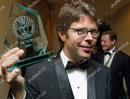 """SOLOMON, FRANZEN Novelist Jonathan Franzen poses with his National Book Award as fellow winner Andrew Solomon passes behind him after the 2001 National Book Foundation's awards cermony in New York, . Franzen won the top prize for fiction with his book, """"The Corrections,"""" while Solomon won for nonfiction with """"The Noonday Demon: An Atlas of Depression"""