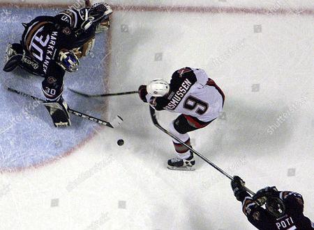 POTI MARKKANEN RASMUSSEN Edmonton Oilers goalie Jussi Markkanen stops a shot by Buffalo Sabres' Erik Rasmussen (9) as Oilers' Tom Poti (5) skates in to help in Buffalo, N.Y., . The Oilers shut out the Sabres 3-0