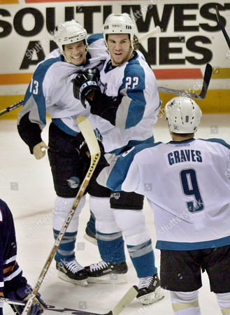 HANNAN HARVEY GRAVES San Jose Sharks defenseman Scott Hannan (22) is congratulated by right wing Todd Harvey, left, and left wing Adam Graves, lower, after Hannan scored the winning goal against the Edmonton Oilers in the third period, in San Jose, Calif. The Sharks beat the Oilers 4-3