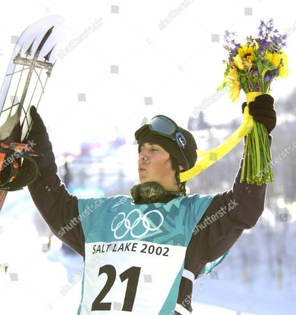 KASS USA's Danny Kass raises his snowboard and bouquet in celebration on the podium, having won the silver medal for the men's halfpipe competition, in Park City, Utah
