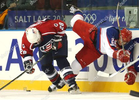 BURE DEADMARSH Russia's Valeri Bure (20), right, is slammed into the boards by Adam Deadmarsh (28) of the United States during first period action in the men's semifinal hockey match at the Winter Olympics in Kearns, Utah