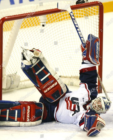 RICHTER U.S. goalie Mike Richter spreads out but the puck gets behind him for a second period goal by Russia's Valeri Bure in their Olympic match in Kearns, Utah