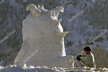 Mark Mason works on a snow sculpture for internet company Monster.com, in Park City, Utah, . The 2002 Salt Lake City Winter Olympics start on Friday