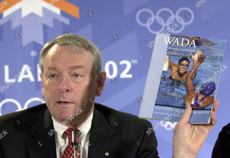 Pound World Anti-Doping Agency Chairman Dick Pound displays the agency's report at a press conference at the Winter Olympic media center in Salt Lake City . The Salt Lake City Winter Olympics begin on Friday Feb. 8