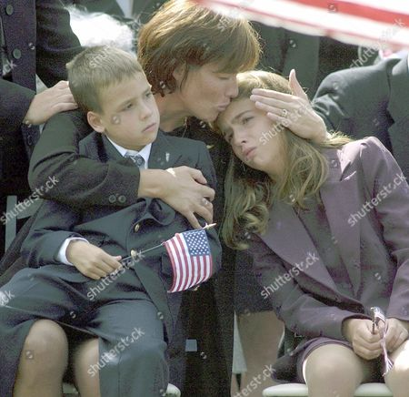 "HORROCKS Miriam Horrocks clutches her son Michael, 6, and kisses her daughter Christa, 9, during a military service in Media, Pa. for her husband Michael R. Horrocks. Military officials presented a 21-gun salute and a solo trumpeter played ""Taps"" at the ceremony for Horrocks, the first officer on the hijacked United Airlines flight that crashed into the south tower of the World Trade Center last week. Horrocks, 38, of Glen Mills, Pa., was a star small-college quarterback at West Chester University and a Marine"